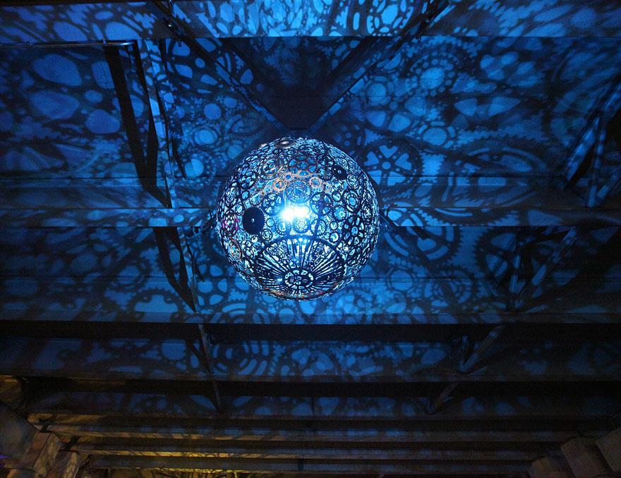Foto del lampadario creato con ingranaggi di bicicletta acceso n.03