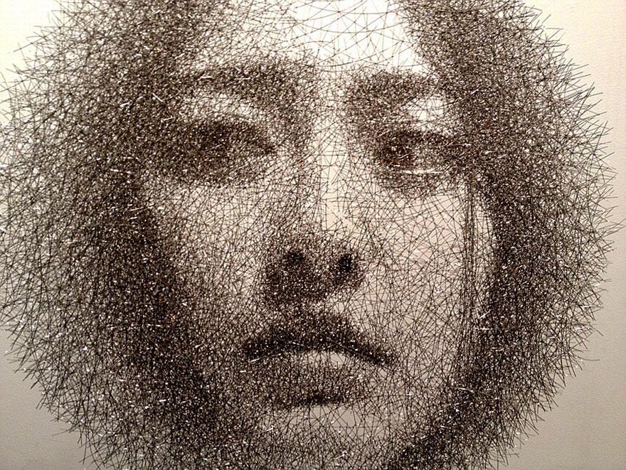 Scultura di un volto realizzata con fili di ferro