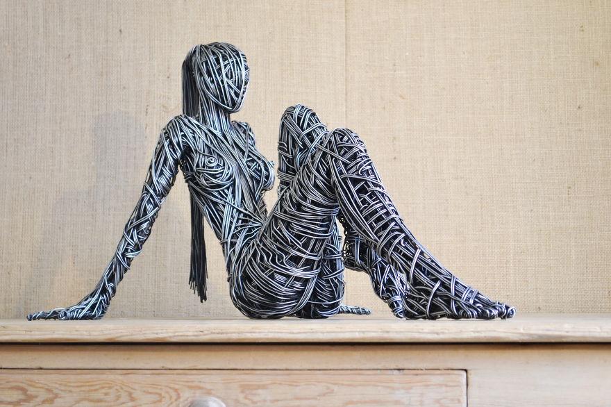 Scultura con filo di ferro di donna seduta