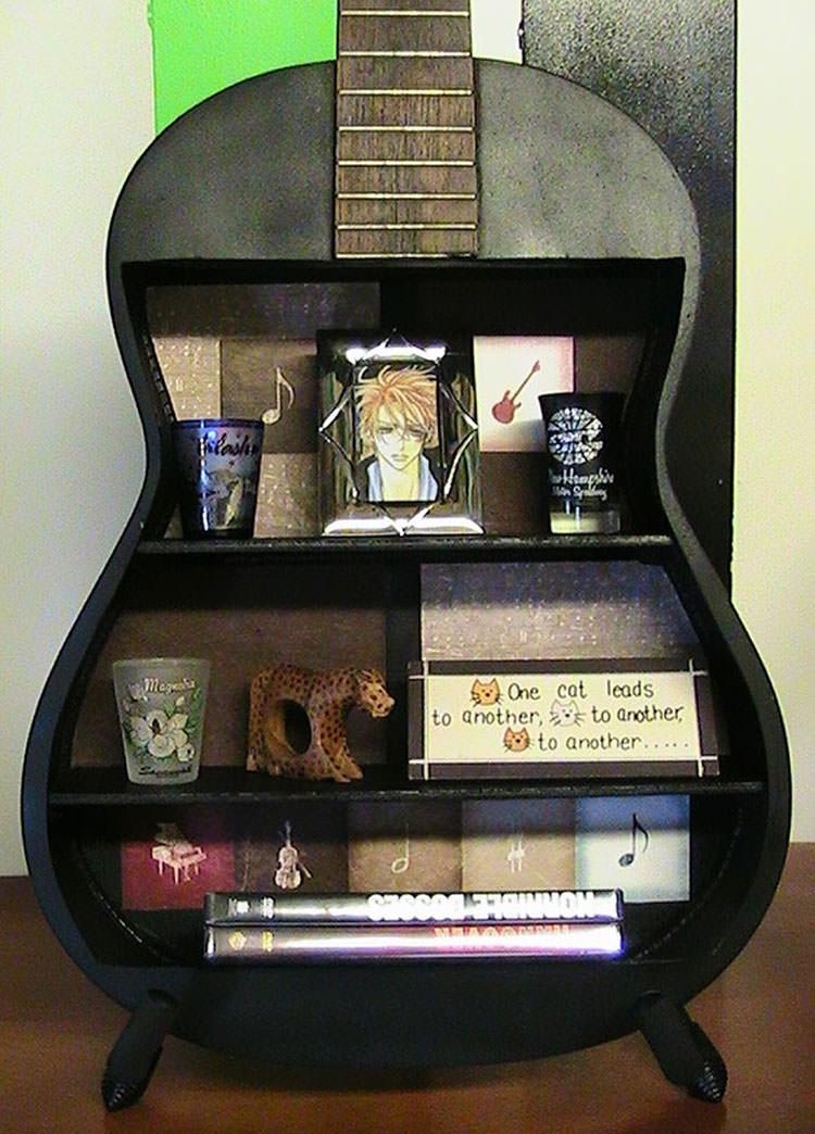 Vecchia chitarra trasformata in uno scaffale
